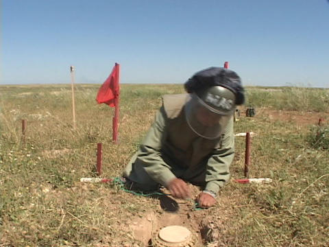 A land mine removal expert prepares to remove a land mine... Stock Video Footage