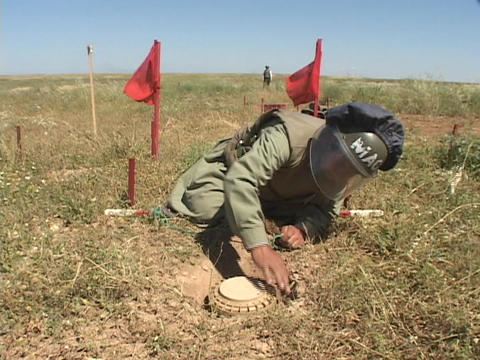 A land mine removal expert prepares to remove a land mine in Iraq Footage