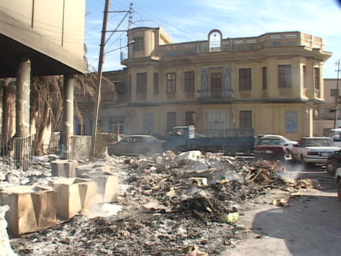 Rubble from a blown up building smolders after a car... Stock Video Footage