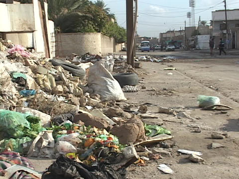 Trash fills the sidewalks and falls into the streets in war-torn Baghdad, Iraq Footage