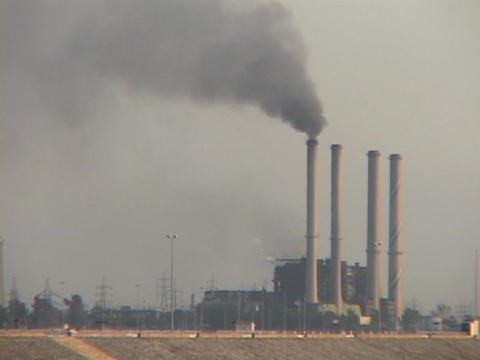 An Iraqi power plant, with only one smokestack working, spews smoke over Baghdad Footage