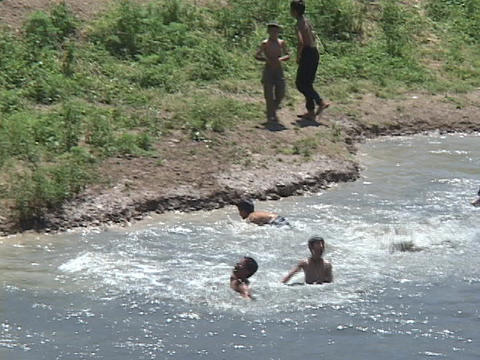 Young boys jump into a river for fun in Iraq Footage