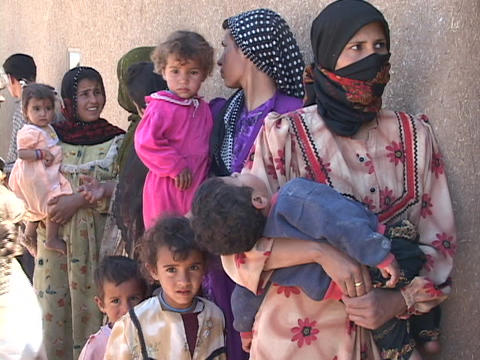 Women and children wait to get into a rural medical clinic in Iraq Live Action