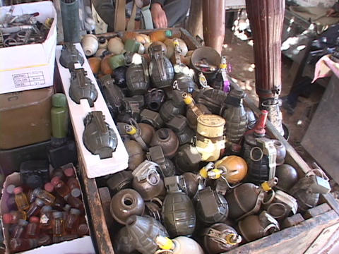 A weapons dealer watches over a pile of grenades in Northern Iraq Footage