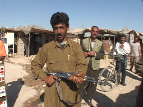 An Iraqi man poses with his rifle but smiles and waves to... Stock Video Footage