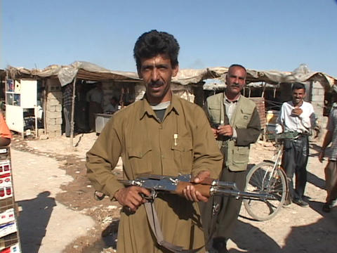 An Iraqi man poses with his rifle but smiles and waves to show he is friendly Footage