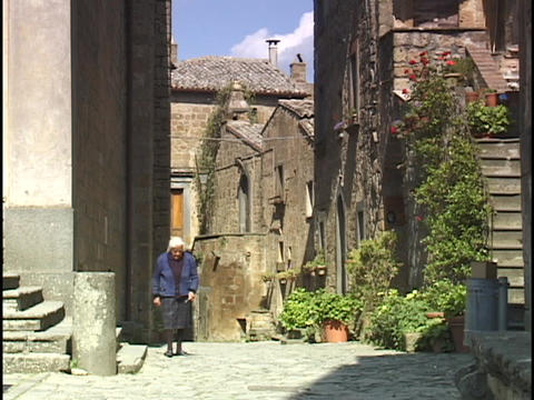 An old woman takes a walk in an Italian village Stock Video Footage