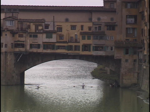 A man rows under a bridge in Florence Stock Video Footage