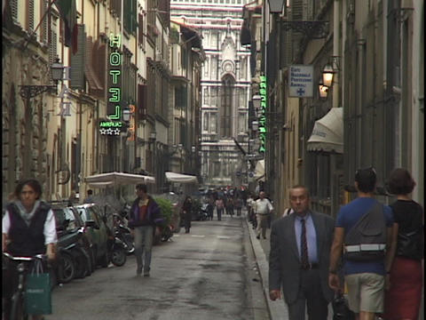 Pedestrians walk down a narrow street in Florence Stock Video Footage