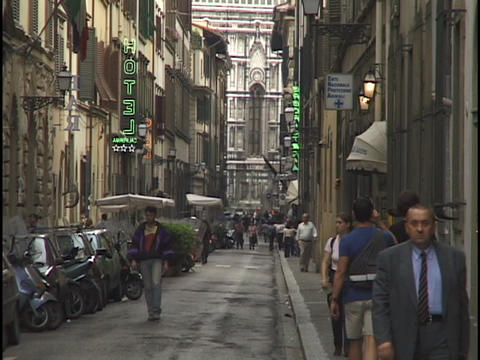 Pedestrians walk down a narrow street in Florence Live Action