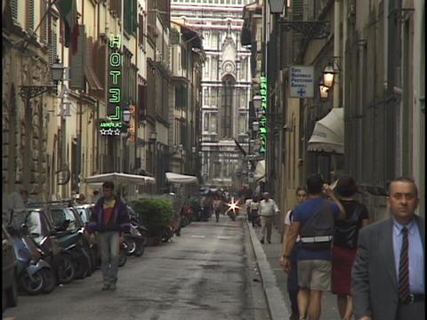 Pedestrians walk down a narrow street in Florence Stock Video Footage