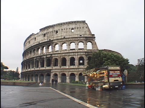 A vendor sells souvenirs next to the Coliseum in Rome Footage