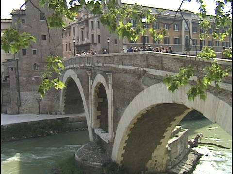 Pedestrians cross a stone bridge over the Tiber River Stock Video Footage