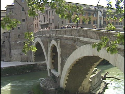 Pedestrians cross a stone bridge over the Tiber River Live Action