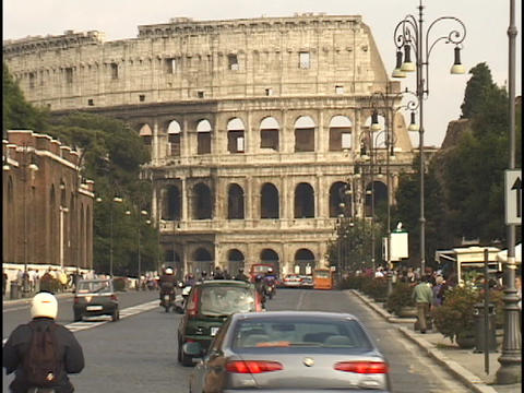 Traffic travels down a street in front of the Coliseum Footage