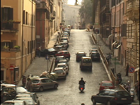 Traffic travels down a narrow street in Rome Footage