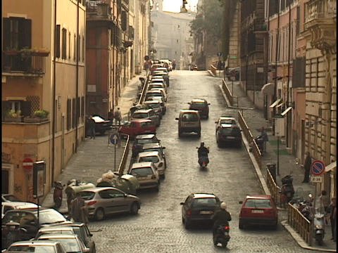 Traffic travels down a narrow street in Rome Stock Video Footage