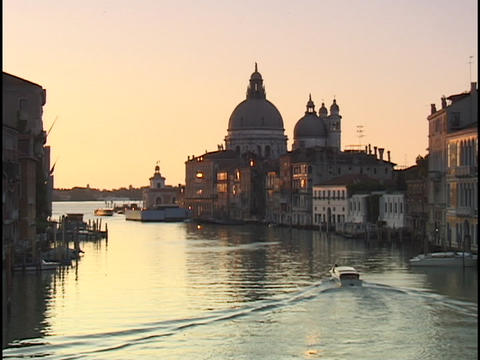 A small boat motors through the Grand Canal, passing in front of the Santa Maria del Salute in Venic Footage