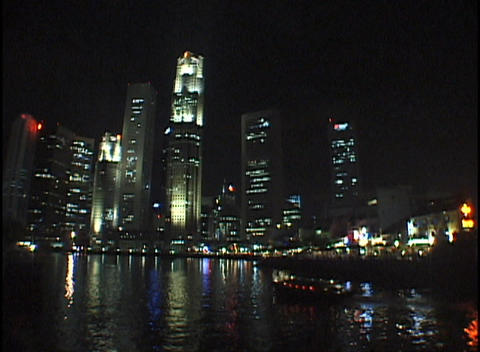 A city skyline reflects in a calm body of water Footage