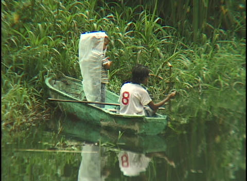 young boys fish from a tiny boat on the verdant banks of... Stock Video Footage
