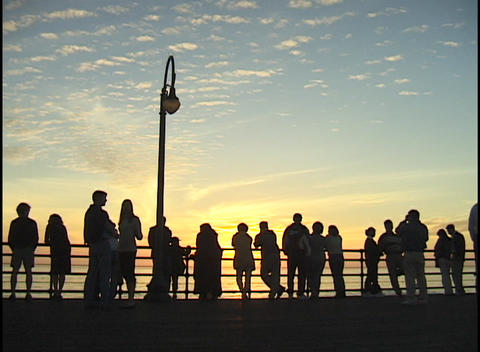 A crowd of people stand on a pier Footage