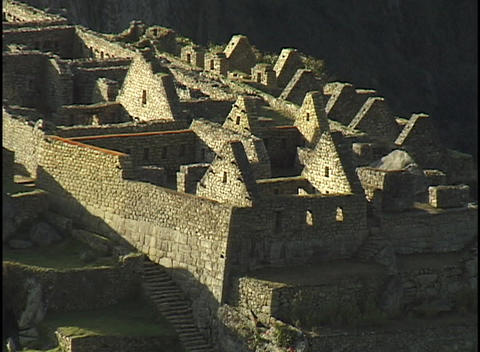 Stone walls and peaked rooftops line the hillsides at the ancient ruins of Machu Picchu Footage