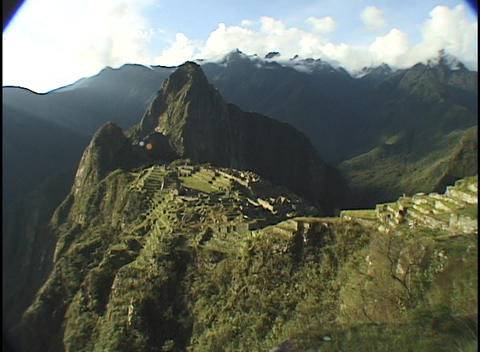 The ancient ruins of Machu Picchu nestle between the steep mountain ridges of Peru Footage