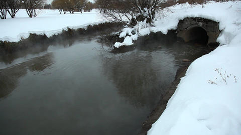 Stream flow from outlet pipe to dark brook, black water bicker over snow banks Footage