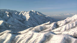 Aerial shot of snowy mountains with salt lake valley in the distance ภาพวิดีโอ