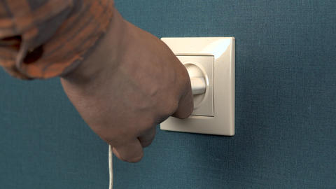 A man pulls out a phone charger from a wall outlet. Rosette in the wall with Live Action
