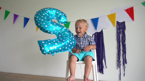 Playful male toddler smile and play with number two balloon at birthday party Live Action