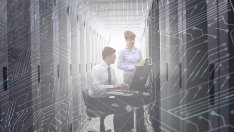 Man and woman working in computer server room while a glowing circuit board moves in foreground Animation