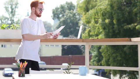 Young Designer Reading Documents, Standing in Balcony Outdoor Footage