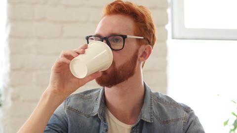 Man Taking Sip of Coffee, Sitting in Office Footage