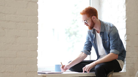 Designer Working on New Design, Sitting in Window, w/ Red Hars and Beard Footage