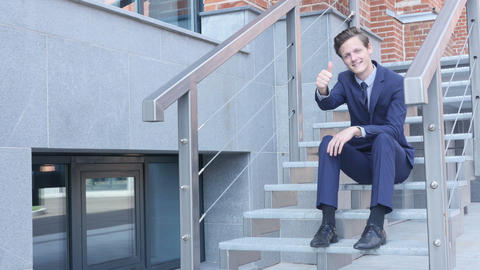 Thumbs Up by Young Businessman Sitting on Stairs Outside Office Footage