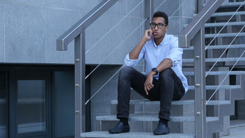 Young Black Man Sitting on Stairs and Talking on Phone Footage