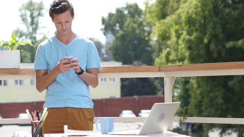 Sunny Day, Man Standing and Using Smartphone in Balcony Footage