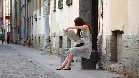 Cheerful tourist girl get lost in old town sit awhile to study map Footage