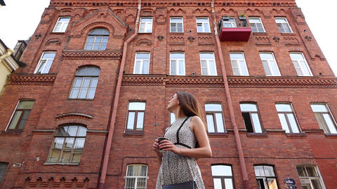 Tourist girl look around, turn against red brick facade building at old town Footage