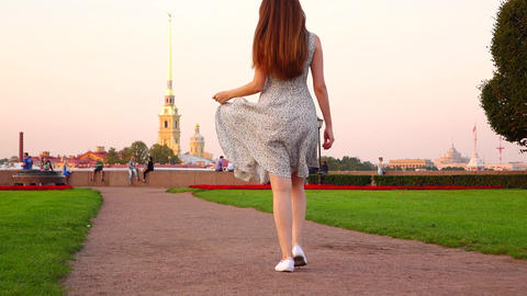 Happy travel girl in dress stroll and spin around at Spit of Vasilyevsky Island Footage