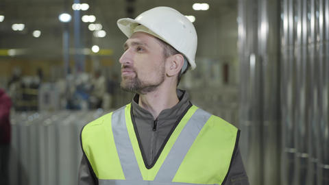 Exhausted Caucasian man in helmet and vest rubbing eyes and stretching at Live Action