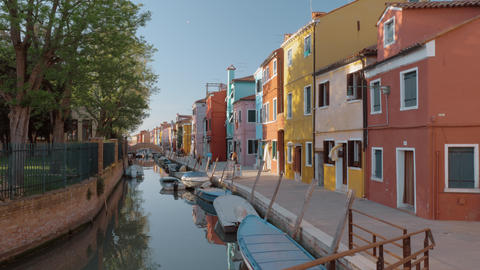 Waterside street with brightly painted houses and walking people. Burano, Italy Acción en vivo