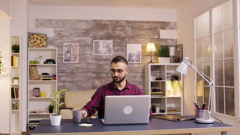 Handsome caucasian freelancer working on laptop from home Live Action