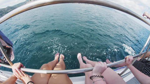 Women's feet sway merrily over the waves dangling from the side of the yacht Live Action