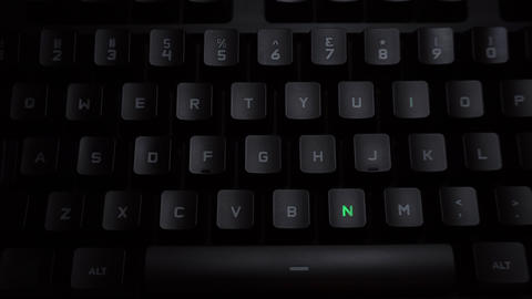 The word nice is typed on a luminous computer keyboard. Black backlit keyboard Live Action