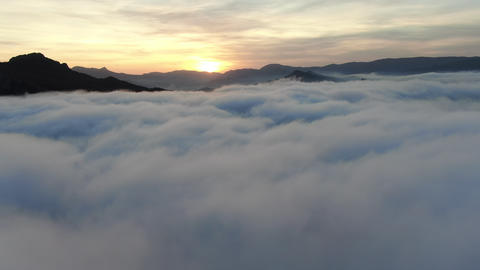 Flights over clouds and mountain peaks at sunset Live Action