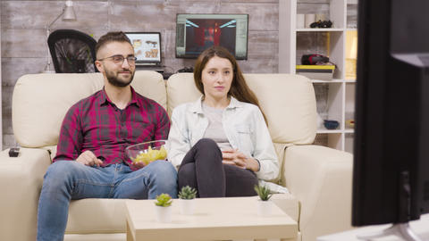 Charming young couple sitting on the couch and watching tv Live Action