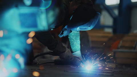skilled employee welds details on floor in workshop closeup Live Action