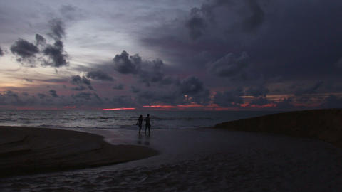 A couple walking on the beach at sunset Footage